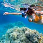 woman-snorkeling-above-coral-reef